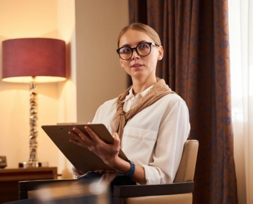 Young beautiful businesswoman in glasses bis sitting in hotel room   Feature   How To Write a Great Property Description For A Vacation Rental