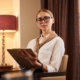 Young beautiful businesswoman in glasses bis sitting in hotel room | Feature | How To Write a Great Property Description For A Vacation Rental