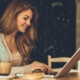 a girl is sitting on table and typing on her laptop with the coffee beside | feature | How to Write And Edit Captions for Your Rental Portfolio