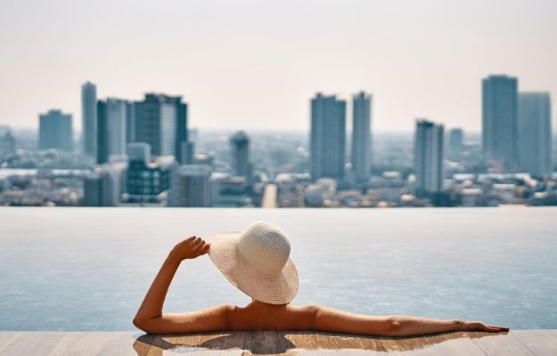 a girl wearing hat is enjoying the view of the city on the rooftop pool   Describe the Experience   How to Write And Edit Captions for Your Rental Portfolio