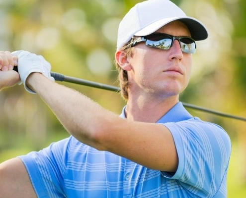 a man making a golf swing wearing blue polo, glasses and hat   Feature   The X Best Golf Courses in Arizona