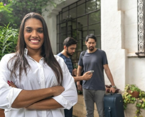 a woman standing in front of her house and 2 guys standing behind and bringing luggage   Feature   How To Write A Good Host Profile: 7 Things To Include
