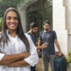 a woman standing in front of her house and 2 guys standing behind and bringing luggage | Feature | How To Write A Good Host Profile: 7 Things To Include