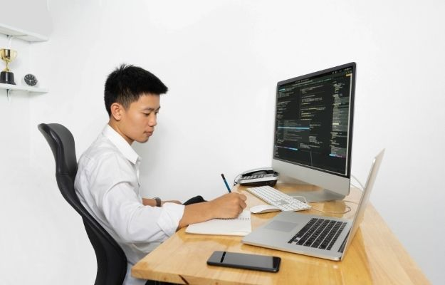 A man is writing on the notebook with a screen having code | Stay Ahead of the Competition |