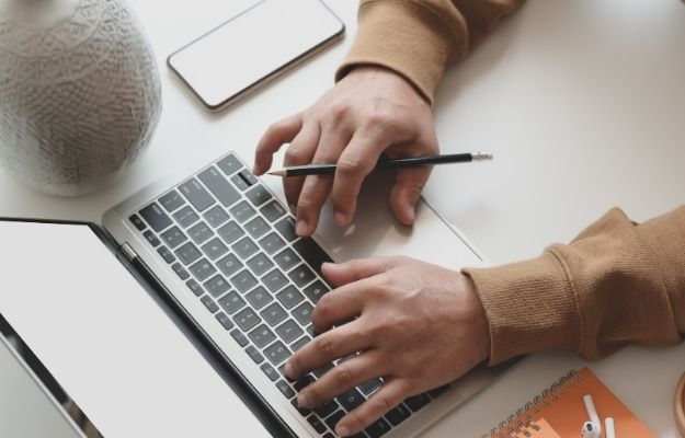 a person is holding a pen and typing on the laptop | What Exactly Is Channel Management? | 3 Ways Your Vacation Rental Could Benefit from Channel Management