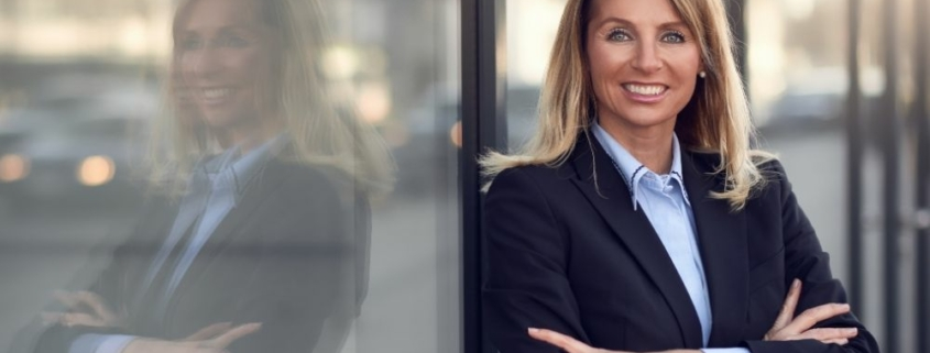 a suited woman leaning on the door and smiling | Feature | Tips For Property Management Marketing