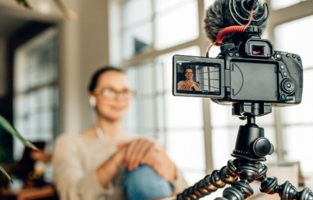 a woman is recording by camera   Video Scripts   Boost Your Vacation Rental Bookings With A Website Or Blog
