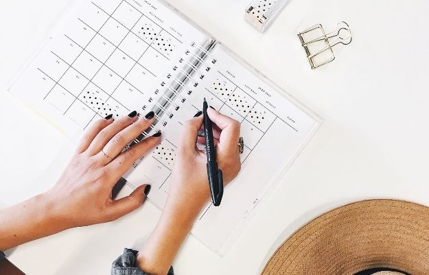 hand holding a pen and writing on the notebook | Make a content marketing plan | Tips For Property Management Marketing